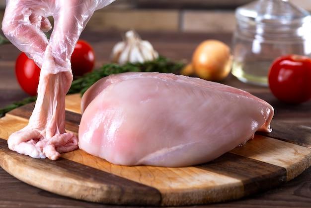 Surowe piersi z kurczaka na desce do krojenia bez skóry