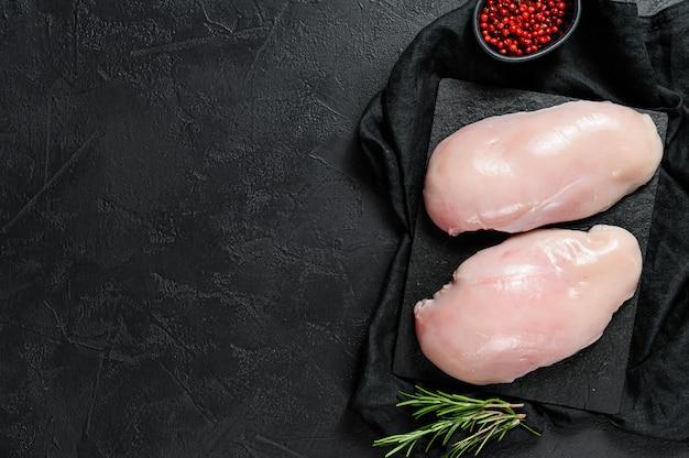 Surowe piersi z kurczaka na desce do krojenia. świeży filet. czarne tło. miejsce na tekst
