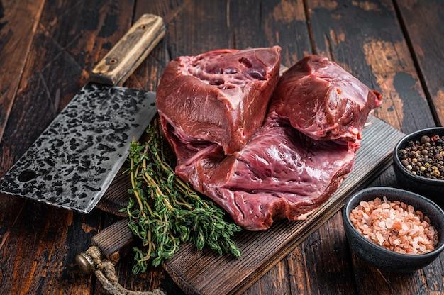 Surowe plasterki wołowiny lub cielęciny serca na desce do krojenia z tasakiem do mięsa. ciemne drewniane tło. widok z góry.