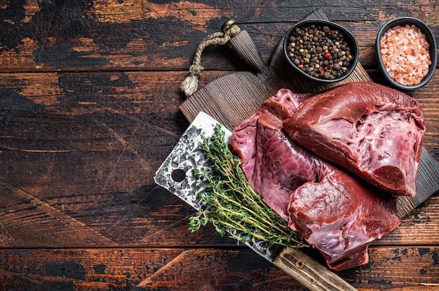 Surowe plasterki wołowiny lub serca cielęcego na desce do krojenia z tasakiem do mięsa