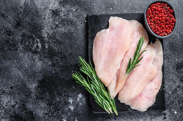 Surowe plastry filetów z piersi kurczaka na marmurowej desce. czarne tło. widok z góry. skopiuj miejsce.