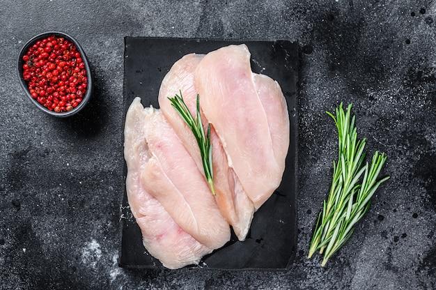 Surowe plastry filetów z piersi kurczaka na marmurowej desce