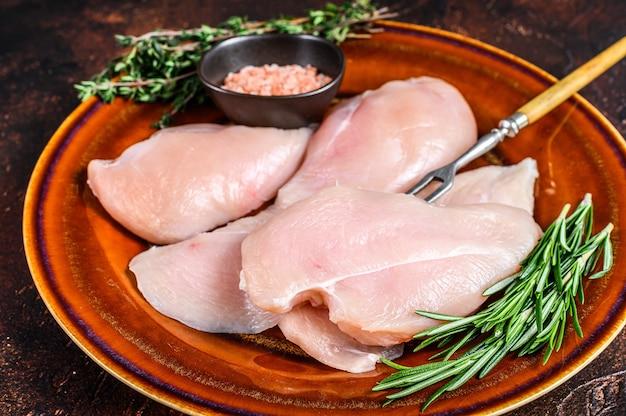 Surowe plastry steków z piersi kurczaka na rustykalnym talerzu z ziołami. ciemne tło. widok z góry.