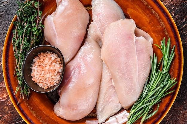 Surowe plastry steków z piersi kurczaka na rustykalnym talerzu z ziołami