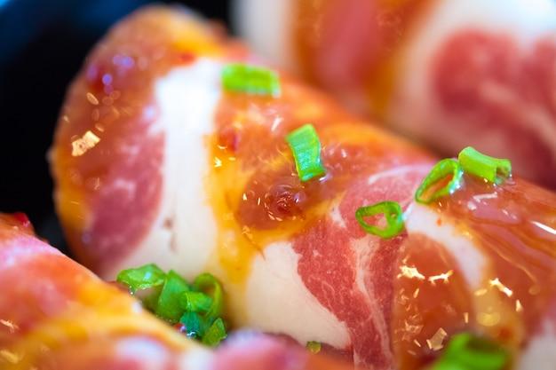 Surowe plastry wieprzowe kurobuta na talerzach, na sukoyaki i yakiniku shabu w gorącym garnku, japońskie jedzenie