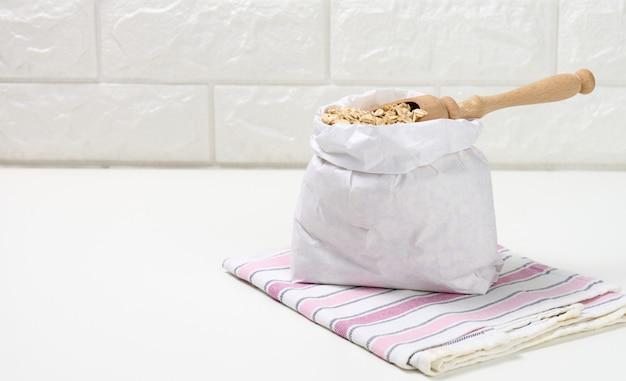 Surowe płatki owsiane w białej papierowej torbie i drewnianą łyżką na białym stole, owsianka śniadaniowa, miejsce na kopię