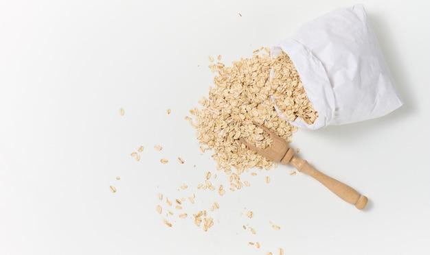 Surowe płatki owsiane w białej papierowej torbie i drewnianą łyżką na białym stole, śniadaniowa owsianka, widok z góry