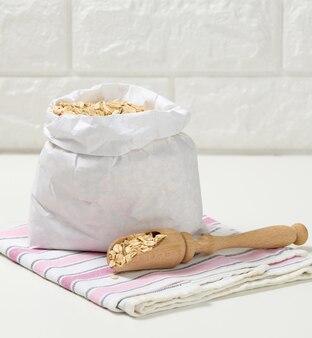 Surowe płatki owsiane w białej papierowej torbie i drewnianą łyżką na białym stole, śniadaniowa owsianka