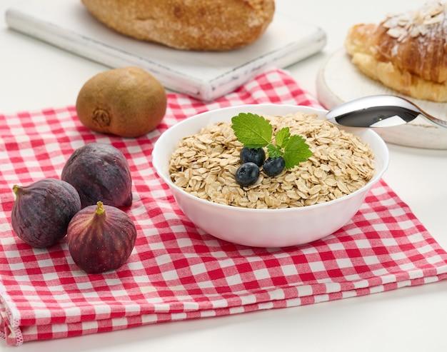 Surowe płatki owsiane w białym talerzu ceramicznym i owoce na białym stole, śniadanie