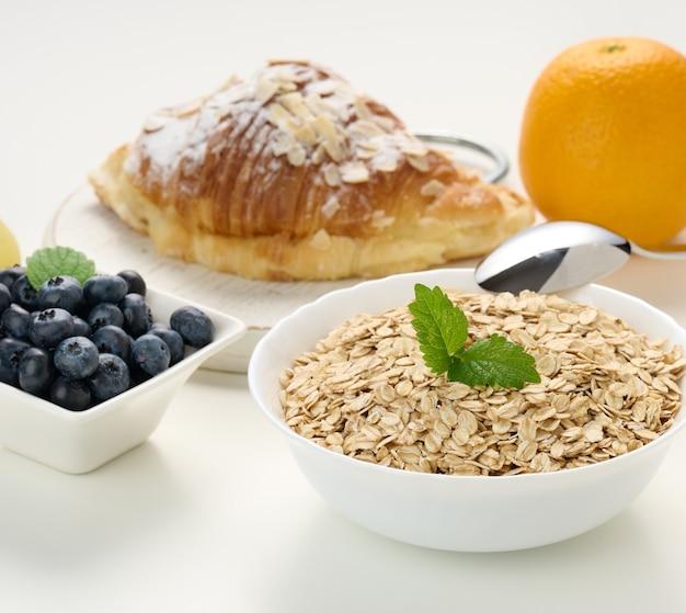 Surowe płatki owsiane w białym talerzu ceramicznym, jagoda, pomarańcza, na białym stole, śniadanie