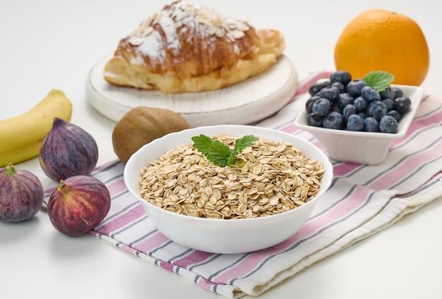 Surowe płatki owsiane w białym talerzu ceramicznym, jagody, figa, pomarańcza, banan, na białym stole, śniadanie