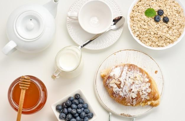 Surowe płatki owsiane w białym talerzu ceramicznym, jagody, miód na białym stole, śniadanie. widok z góry