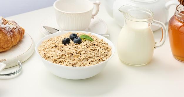 Surowe płatki owsiane w białym talerzu ceramicznym na białym stole, śniadanie, zbliżenie