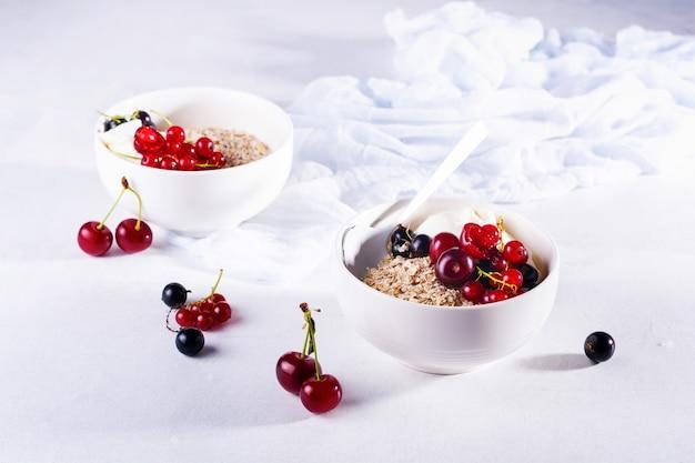 Surowe płatki owsiane z jogurtem i jagodami wiśni, porzeczek i jagód do przygotowania zdrowego śniadania w białej ceramicznej misce na jasnym tle