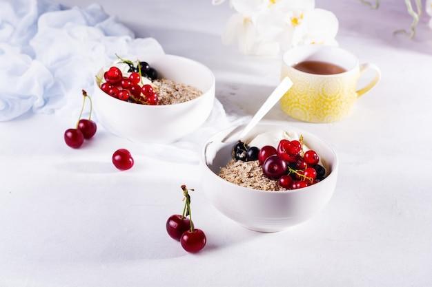 Surowe płatki owsiane z jogurtem i jagodami wiśni, porzeczek i jagód do przygotowania zdrowego śniadania w białej ceramicznej misce na świetle