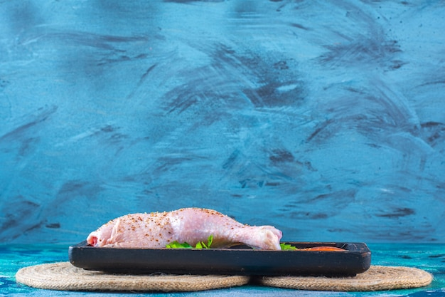 Surowe podudzia z kurczaka marynowane z pomidorami w drewnianym talerzu na trójkącie