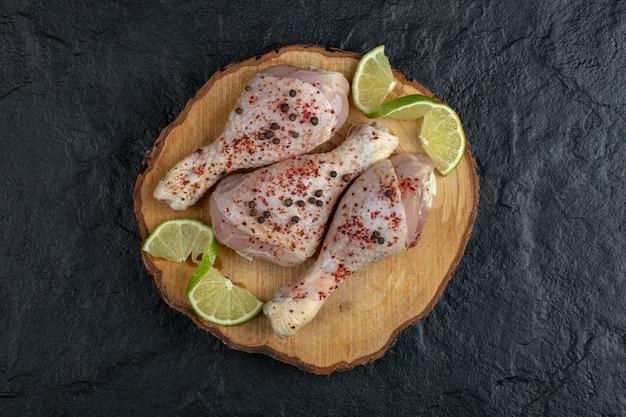 Surowe podudzia z kurczaka na desce.