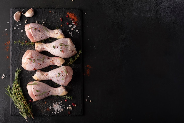 Surowe podudzia z kurczaka z przyprawami i ziołami na czarnej tablicy, widok z góry