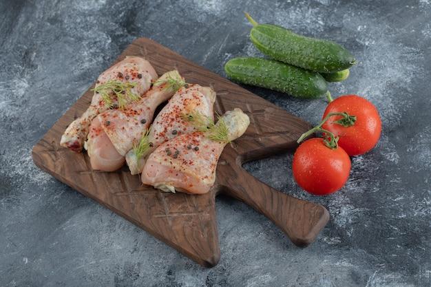 Surowe podudzia z kurczaka ze świeżymi pomidorami i ogórkiem na szarym tle.
