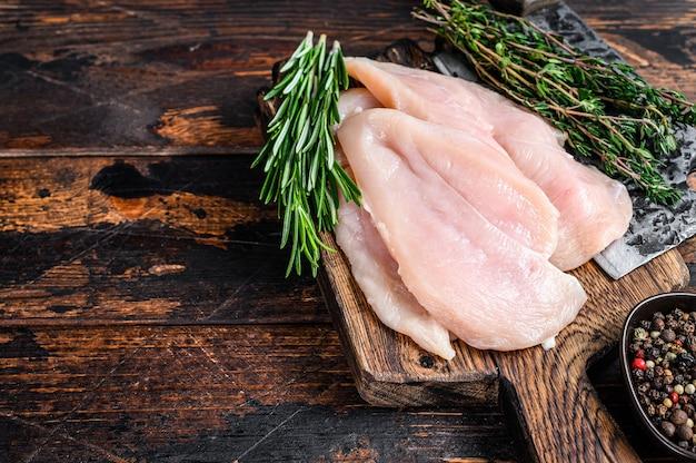 Surowe pokrojone kotlety z fileta z piersi kurczaka na drewnianej desce do krojenia z tasakiem. ciemne tło drewniane. widok z góry. skopiuj miejsce.
