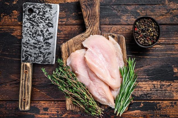Surowe pokrojone kotlety z fileta z piersi kurczaka na drewnianej desce do krojenia z tasakiem. ciemne tło drewniane. widok z góry.