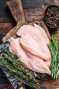 Surowe pokrojone kotlety z fileta z piersi kurczaka na drewnianej desce do krojenia z tasakiem