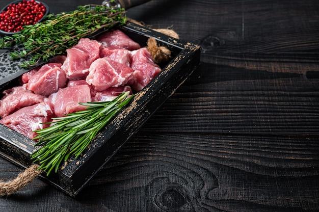 Surowe pokrojone w kostkę mięso z młodych wieprzowiny z przyprawami w rustykalnej tacy. czarne drewniane tło. widok z góry. skopiuj miejsce.