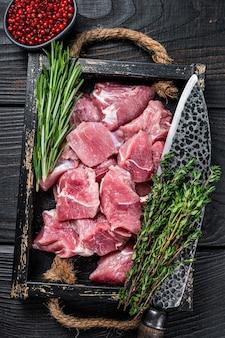 Surowe pokrojone w kostkę mięso z młodych wieprzowiny z przyprawami w rustykalnej tacy. czarne drewniane tło. widok z góry.