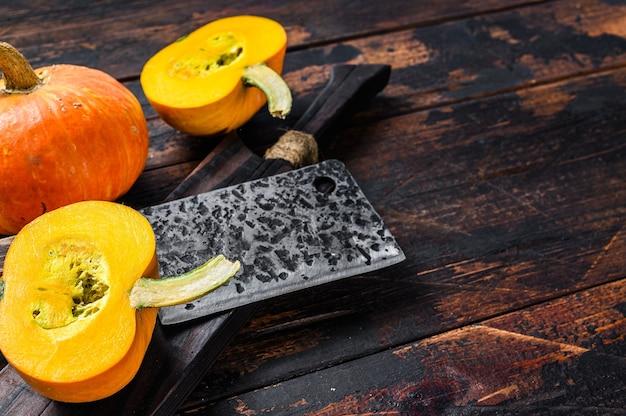 Surowe pomarańczowe dynie. ciemne tło drewniane