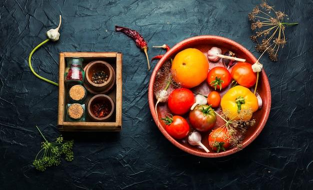 Surowe pomidory i składniki do gotowania marynowanych pomidorów