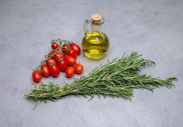 Surowe pomidory koktajlowe oliwa z oliwek i rozmaryn na betonowym tle