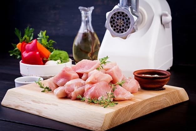 Surowe posiekane filety z piersi kurczaka na drewnianej desce do krojenia i maszynce do mięsa