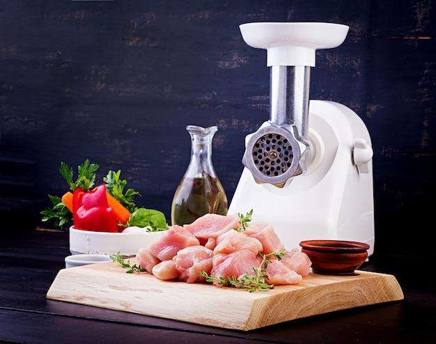 Surowe posiekane filety z piersi kurczaka na drewnianej desce do krojenia i maszynce do mięsa.