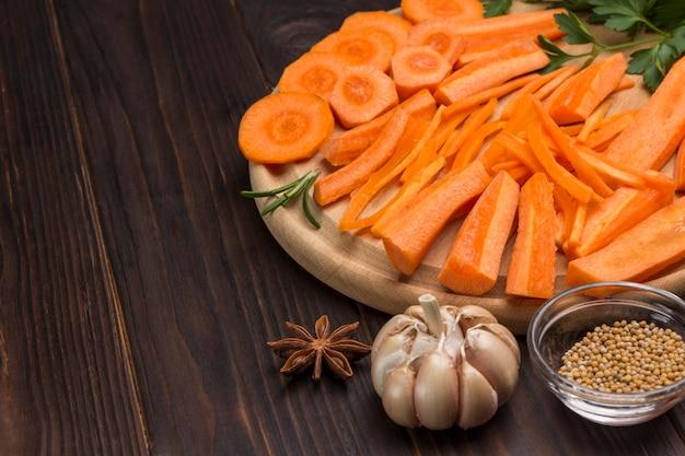 Surowe posiekane marchewki na desce do krojenia. czosnek i nasiona gorczycy na stole. naturalne zbliżenie. skopiuj miejsce