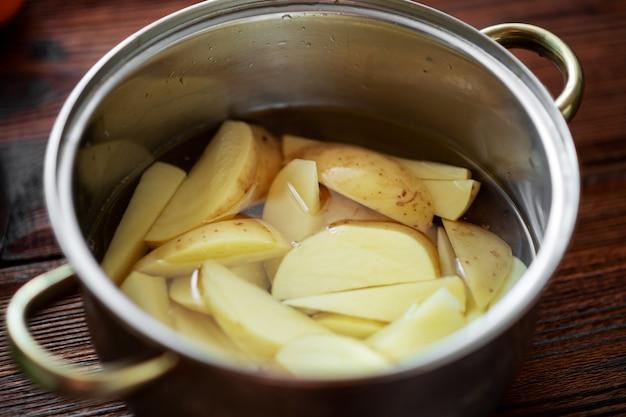 Surowe posiekane ziemniaki w garnku z wodą. przygotowanie do gotowania.
