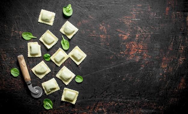 Surowe ravioli z zieleniną na rustykalnym stole