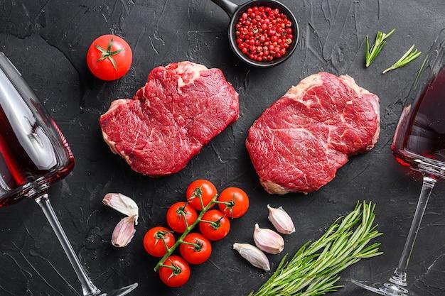 Surowe rumsztyki z organicznych kawałków mięsa wołowego w pobliżu kieliszków do czerwonego wina z rozmarynem, czosnkiem i przyprawami na czarnym tle z teksturą, widok z góry.