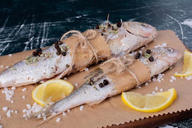 Surowe ryby całe z plasterkami cytryny, ziarnami pieprzu i solą na desce.