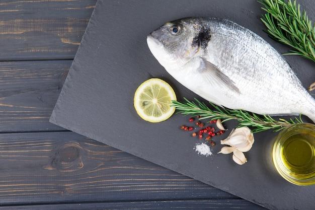 Surowe ryby dorado gotowania i składników. dorado, cytryna, pomidor, zioła i przyprawy. widok z góry na stół z drewna