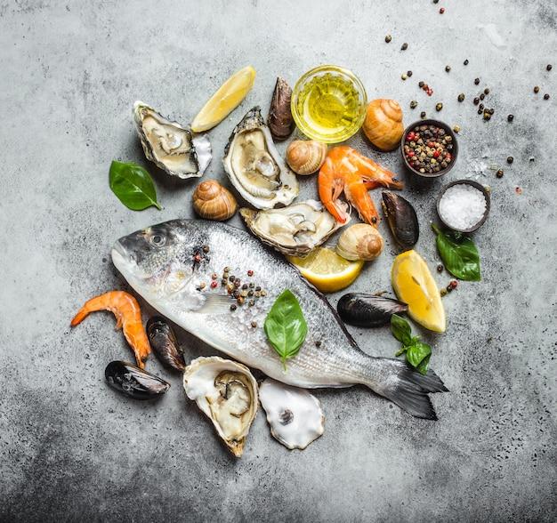 Surowe ryby dorado i świeże ostrygi z owoców morza, krewetki, małże, małże, muszle z cytryną, oliwa z oliwek, zioła na szarym kamiennym tle rustykalnym
