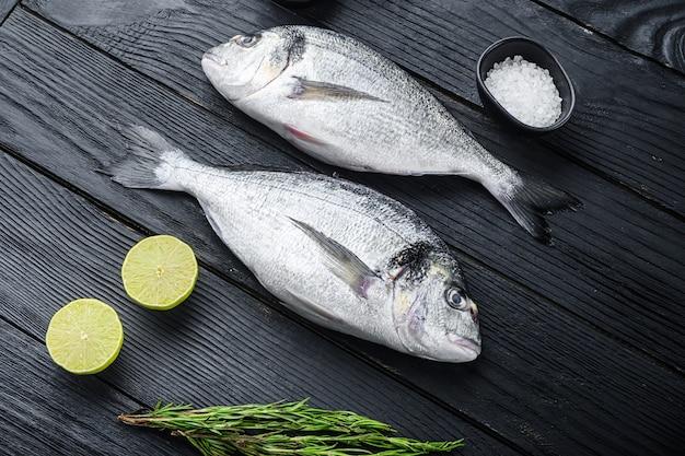 Surowe ryby dorado lub dorada cała para z ziołami do grilla niegotowane na widok z boku czarny drewniany stół.