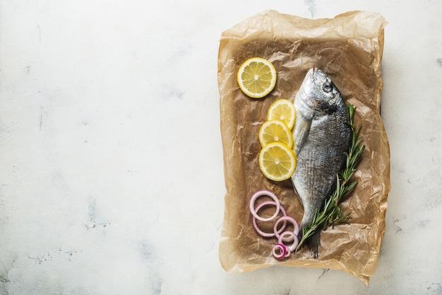Surowe ryby dorado na starej drewnianej desce do krojenia przygotowane do gotowania z plasterkami cytryny, cebuli, przypraw i oleju. widok z góry na białym tle. skopiuj miejsce.