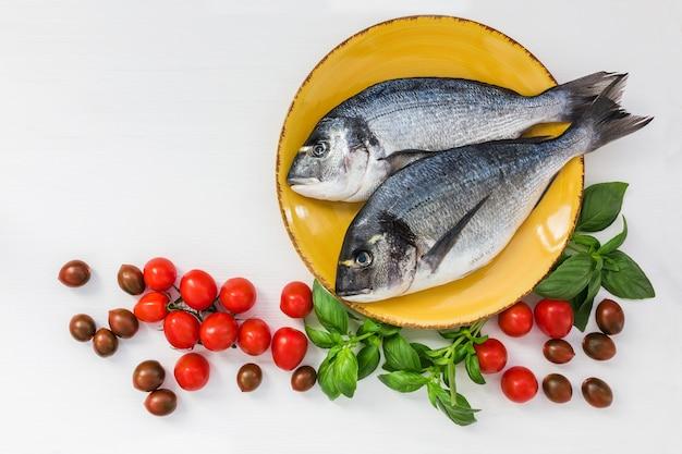 Surowe ryby dorado na żółtym talerzu. widok z góry, miejsce na kopię