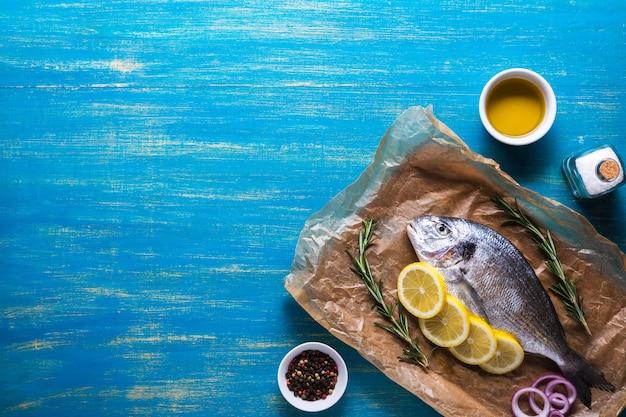 Surowe ryby dorado przygotowane do gotowania z plasterkami cytryny, rozmarynu, cebuli, przypraw i oleju na niebieskim tle. widok z góry. skopiuj miejsce.