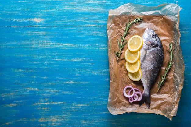 Surowe ryby dorado przygotowane do gotowania z plastrami cytryny, rozmarynu i cebuli na niebieskim tle. widok z góry. skopiuj miejsce.