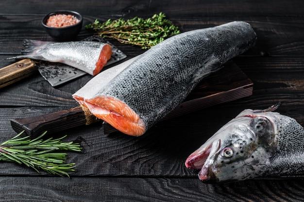 Surowe ryby łososia na drewnianej desce do krojenia z tasakiem szefa kuchni. czarne drewniane tło. widok z góry.