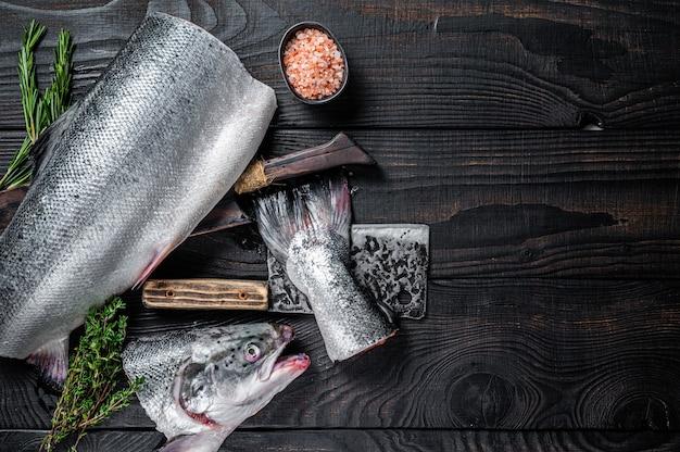 Surowe ryby łososia pokrojone na drewnianej desce do krojenia z tasakiem szefa kuchni. czarne drewniane tło. widok z góry. skopiuj miejsce.