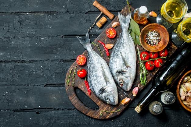 Surowe ryby morskie dorado z kieliszkami białego wina. na czarnym tle rustykalnym