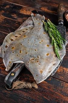 Surowe ryby płastugi na desce rzeźniczej z nożem