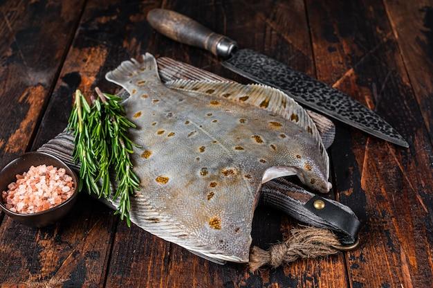 Surowe ryby płastugi na pokładzie rzeźnika z nożem. ciemne drewniane tło. widok z góry.